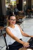 工作在网上在一个室外咖啡馆的典雅的女商人 免版税图库摄影