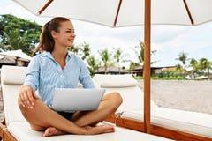工作在网上在海滩的女商人 自由职业者的计算机互联网 库存图片
