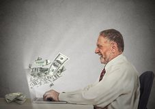 工作在网上在计算机收入金钱的微笑的商人 免版税库存图片