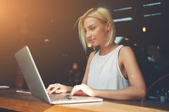 工作在网书的美丽的白种人妇女在咖啡馆酒吧的早晨早餐期间 免版税库存照片