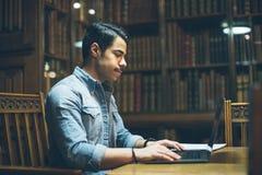 工作在老历史图书馆里的英俊的阿拉伯人 研究教育海外在欧洲 免版税库存图片