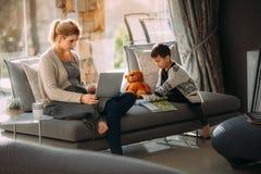 工作在膝上型计算机和儿子读书故事书的母亲 免版税库存图片