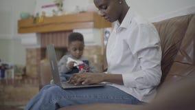 工作在膝上型计算机和她的小逗人喜爱的儿子的非裔美国人的妇女使用与近玩具在舒适客厅 股票视频