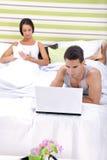 工作在膝上型计算机和妇女阅读书的人在卧室 免版税库存图片