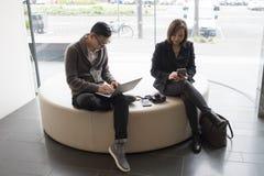 工作在膝上型计算机和手机的男人和妇女 免版税库存照片