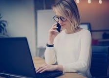 工作在膝上型计算机和打电话的年轻美丽的妇女使用现代智能手机工作场所 水平,弄脏 免版税库存照片