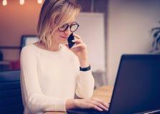 工作在膝上型计算机和打电话的年轻美丽的妇女使用现代智能手机工作场所 水平,被弄脏的背景 库存照片
