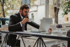 工作在膝上型计算机和饮用的咖啡的商人 免版税库存图片
