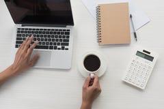 工作在膝上型计算机和饮用的咖啡的女实业家在工作场所 库存照片