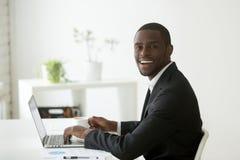工作在膝上型计算机和饮用的咖啡的微笑的黑人工作者 免版税库存照片