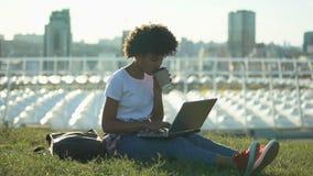 工作在膝上型计算机和饮用的咖啡的美丽的美国黑人的女性自由职业者 股票录像