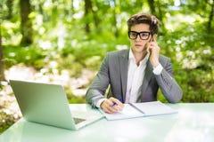 工作在膝上型计算机在办公室桌上和谈话的年轻英俊的商人画象在有costumer的电话在绿色森林公园 Bu 图库摄影