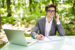 工作在膝上型计算机在办公室桌上和谈话的年轻英俊的商人画象在有costumer的电话在绿色森林公园 Bu 免版税库存照片