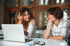 工作在膝上型计算机旁边的两名相当愉快的妇女 免版税库存图片
