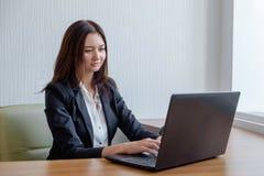 工作在膝上型计算机的办公室的可爱的妇女 免版税图库摄影