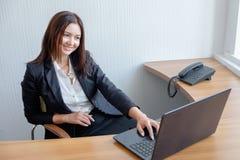 工作在膝上型计算机的办公室的可爱的妇女 免版税库存照片