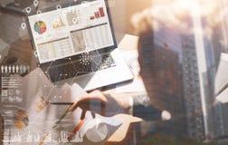 工作在膝上型计算机的办公室的商人 人在手上的拿着纸张文件 数字式屏幕的概念,真正 库存照片