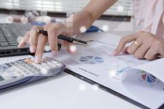 工作在膝上型计算机的办公室的年轻金融市场分析家,当坐在白色桌上时 商人分析文件 免版税库存照片