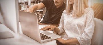 工作在膝上型计算机的图表设计师在书桌 免版税库存图片