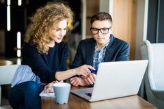 工作在膝上型计算机的小组两个工友在一个现代办公室谈论 在屏幕上指向的妇女 免版税库存照片