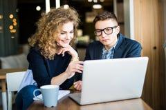 工作在膝上型计算机的小组两个工友在一个现代办公室谈论 在膝上型计算机屏幕读的愉快的妇女 图库摄影