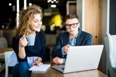 工作在膝上型计算机的小组两个工友在一个现代办公室谈论 妇女饮料咖啡 库存照片