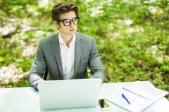 工作在膝上型计算机的年轻英俊的商人在绿色森林企业概念的办公室桌上 免版税库存照片