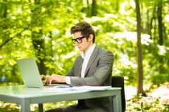 工作在膝上型计算机的年轻英俊的商人旁边画象在办公室桌上在绿色公园 到达天空的企业概念金黄回归键所有权 库存照片