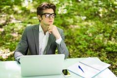 工作在膝上型计算机的年轻英俊的商人画象在办公室在下巴的桌手在绿色公园 到达天空的企业概念金黄回归键所有权 库存图片