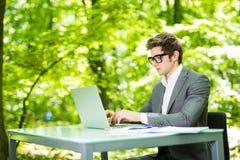 工作在膝上型计算机的年轻英俊的商人画象在办公室桌上在绿色公园 到达天空的企业概念金黄回归键所有权 免版税图库摄影