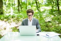 工作在膝上型计算机的年轻英俊的商人画象在办公室桌上在绿色公园 到达天空的企业概念金黄回归键所有权 库存图片