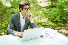 工作在膝上型计算机的年轻英俊的商人画象在办公室桌上用在下巴微笑的手在绿色森林企业concep 库存照片