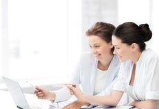 工作在膝上型计算机的微笑的女实业家在办公室 库存图片