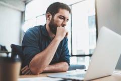工作在膝上型计算机的晴朗的办公室的年轻沉思人,当坐在木桌上时 关于笔记本的商人报告 库存照片