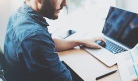 工作在膝上型计算机的晴朗的办公室的年轻沉思人,当坐在木桌上时 关于笔记本的商人报告 图库摄影