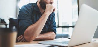工作在膝上型计算机的晴朗的办公室的有胡子的沉思人,当坐在木桌上时 关于笔记本的商人报告 库存图片