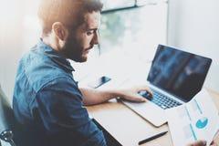 工作在膝上型计算机的晴朗的顶楼办公室的年轻有胡子的人 商人在他的手上分析纸张文件报告 蠢材 免版税库存图片