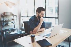 工作在膝上型计算机的晴朗的顶楼办公室的有胡子的沉思工友,当坐在木桌上时 商人读书 免版税图库摄影