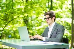 工作在膝上型计算机的英俊的商人画象在办公室桌上在绿色公园 到达天空的企业概念金黄回归键所有权 免版税图库摄影