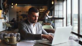工作在膝上型计算机的英俊的年轻商人在餐馆 影视素材