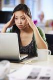 工作在膝上型计算机的被注重的妇女在当代办公室 库存图片