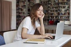 工作在膝上型计算机的,对照相机,镇静面孔,书架的神色共同工作的办公室的少妇长的头发分析家后边,图书馆 库存图片