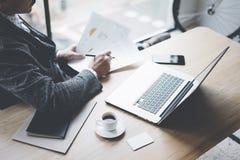 工作在膝上型计算机的晴朗的办公室的成人典雅的银行业务财务分析家,当坐在木桌上时 商人 免版税库存图片