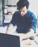 工作在膝上型计算机的晴朗的办公室的年轻可爱的人,当坐在木桌上时 商人分析数字式报告 库存图片