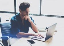 工作在膝上型计算机的晴朗的办公室的年轻沉思人,当坐在木桌上时 商人分析库存报告  库存图片