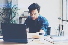 工作在膝上型计算机的晴朗的办公室的年轻英俊的人,当坐在木桌上时 商人分析库存报告  库存图片