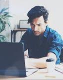 工作在膝上型计算机的晴朗的办公室的年轻英俊的人,当坐在木桌上时 商人分析库存报告  免版税库存图片