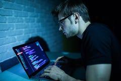 工作在膝上型计算机攻击网络软件的年轻人黑客在夜 免版税库存图片