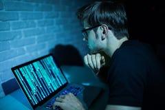 工作在膝上型计算机攻击网络软件的年轻人黑客在夜 免版税库存照片