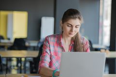 工作在膝上型计算机lndoors的一名严肃的妇女的画象 免版税库存图片